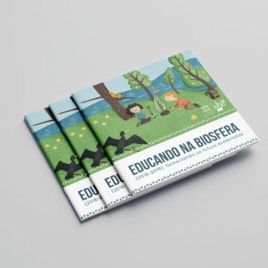 """Varios libros apilados donde puede verse con detalle la Portada del libro """"Educando na Biosfera 2018-2019"""" con una ilustración de unos niño plantando un árbol rodeados de Naturaleza."""
